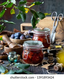 Two glass jars with homemade canned plums jam, marmalade, jelly on rustic wooden table with cardamon, cinnamon,  anise, bowl of plums, spice mortar, spool of thread, bones and branch with green leaves