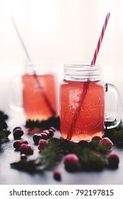 Two glass jars with a hot drink made from cranberries and apples in backlight with straws among fir branches