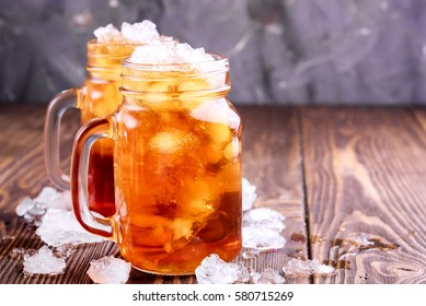 Two glass jars with ice tea. Ice around jars Wooden background Copy space Horizontal photo