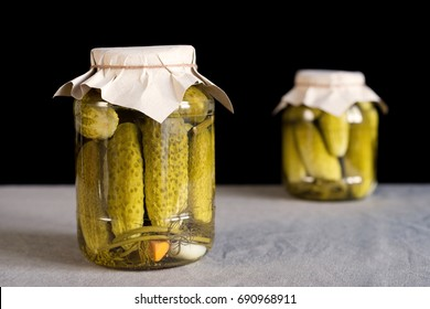 Two glass jars with pickled cucumbers