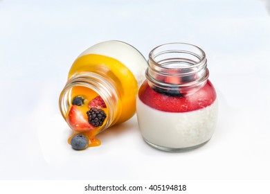 two glass jars with sweet dessert jam and berries