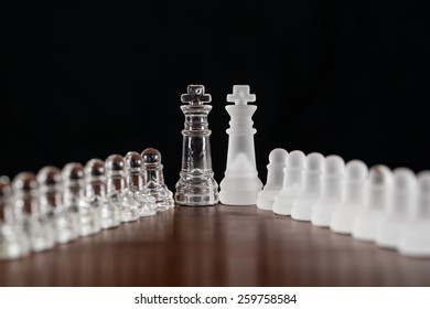 Two glass kings from a chess set on a wood surface.  They are lined up with the pawns flanking into the camera.