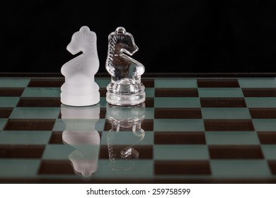 Two glass knight chess pieces on a glass board.