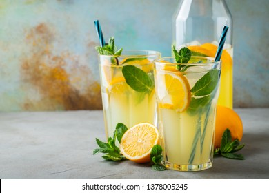 Two glass with lemonade or mojito cocktail with lemon and mint, cold refreshing drink or beverage with ice on rustic blue background. Copy space