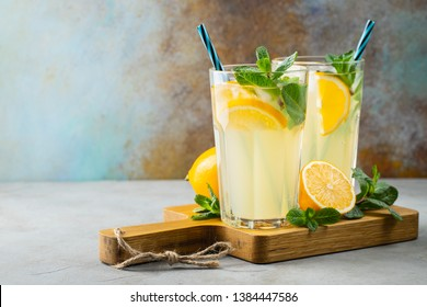Two glass with lemonade or mojito cocktail with lemon and mint, cold refreshing drink or beverage with ice on rustic blue background. Copy space - Shutterstock ID 1384447586