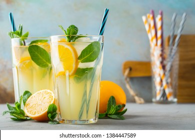 Two glass with lemonade or mojito cocktail with lemon and mint, cold refreshing drink or beverage with ice on rustic blue background