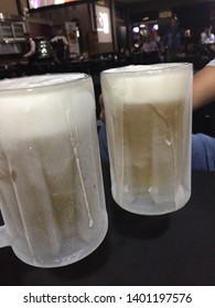 Two glass mug, ultra cold, with chopp and stupidly chilled and very creamy foam, on a wooden table.