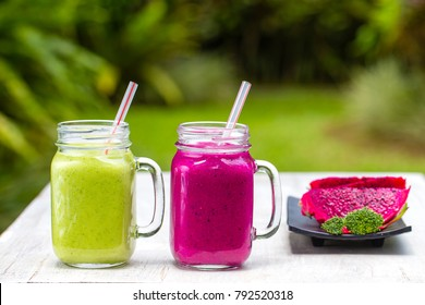 Two glass mugs with fresh smoothies from a dragon fruit, banana, mango, avocado, broccoli and honey. Island Bali, Ubud, Indonesia. Close up