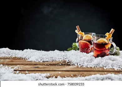Two glass mugs of traditional Christmas hot spicy mulled red wine, or Gluhwein, standing in winter snow on wooden boards with copy space for your holiday greeting