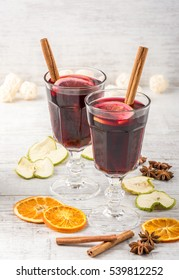 Two glass of mulled wine with cinnamon sticks, dry slice of oranges and apple, star anise on a white table