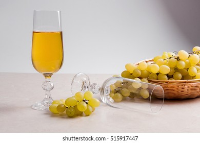 Two glass - one empty and one with white wine on light marble background. Bunch of green grapes in yellow wooden basket near the glasses.