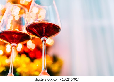 Two glass of red wine in front of christmas tree lights bokeh. New year eve and xmas celebration party. Luxury romantic holiday dinner.