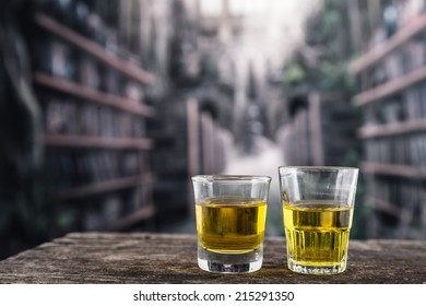 Two glass shots with yellow liqour resembling whiskey, rum, tequila, spirit on wooden table
