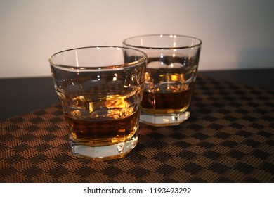 two glasses with alcohol in a table