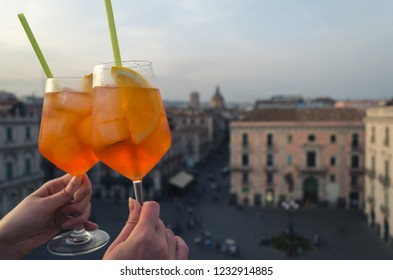 Two glasses of aperol spritz on the roof top of Catania. The city of Catania is blurred at the background.