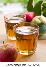 Two glasses of apple juice with apples in the background.