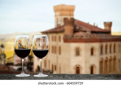 Two glasses of Barolo wine on a windowsill with the castle of Barolo (Piedmont, Italy) blurred on the background
