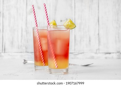Two glasses of Bay Breeze cocktail garnished with lime wedges on wooden background