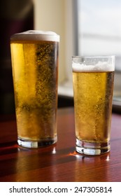 Two glasses of beer by the window