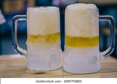 Two Glasses of Beer Freshly Served Cold on Wooden Table Restaurant Blurred Background. Extremely Chilled Beer Served with White Beer Foam in Frozen Beer Mugs as Couple Celebration or Friends Relaxing