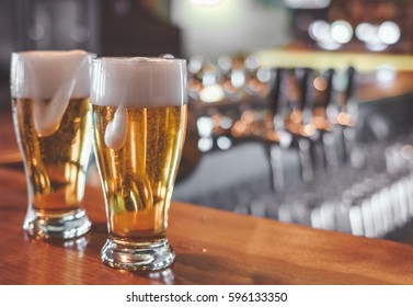 Two  Glasses of Beer on a bar table. Closeup.