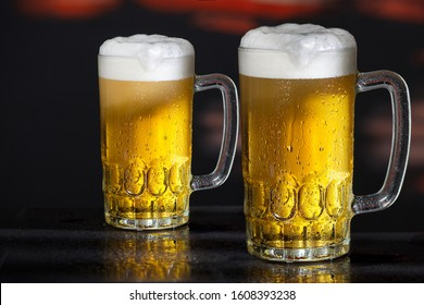 Two glasses of beer on the dark background