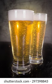 two glasses of beer over vintage background