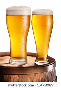 Two glasses of beer over woden barrel. File contains clipping paths.