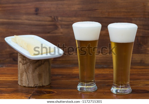 Two glasses of beer and a plate with pieces of cheese