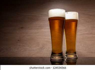 Two glasses with beer served on the table.