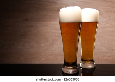 Two glasses of beer served on the table.