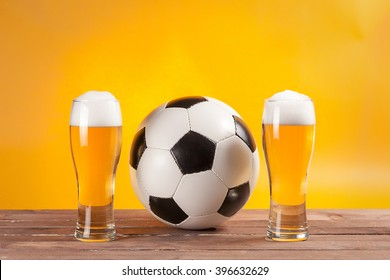 two glasses with beer and soccer ball near tv remote. Free space for text