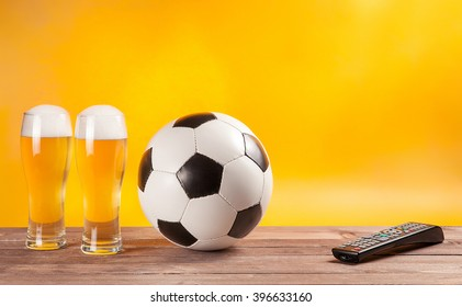 two glasses with beer and soccer ball near tv remote. Free space for text. Yellow backround