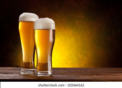 Two glasses of beers on a wooden table. Dark yellow background.