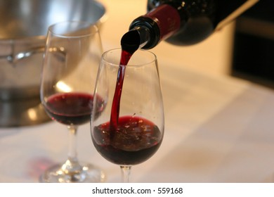 Two glasses being filled with red wine at a tasting event