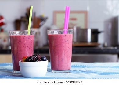 Two glasses of berries smoothies topped with dried fruits and nuts, blue cloth towel