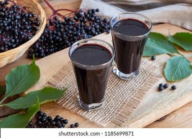 Two glasses of black elder syrup with fresh elderberries