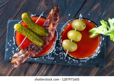 Two glasses of Bloody Mary garnished with gherkins and celery stalk