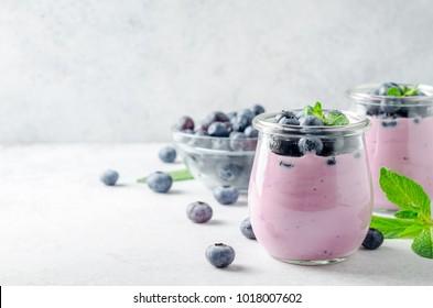 Deux verres de yaourt aux myrtilles avec des myrtilles sur fond gris clair. Vue avant, espace de copie, image horizontale