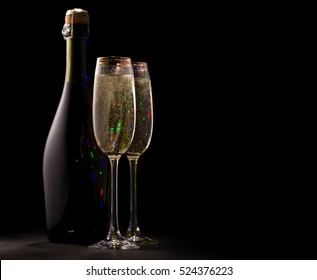 two glasses and a bottle of champagne, bubbles are visible, and highlights the contours, black background