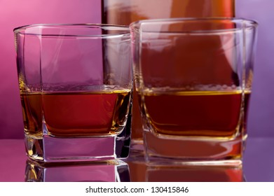 two glasses and a bottle of hard liquor against warm backdrop