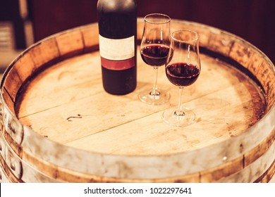 Two glasses and a bottle of port wine on a barrel