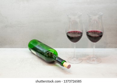 Two glasses and bottle of red wine on gray background