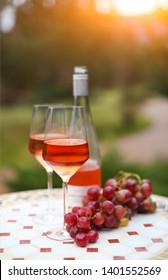 Two glasses and bottle of rose wine in autumn vineyard on marble table. Harvest time, picnic or wine fest theme