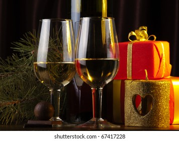 Two glasses and box with gifts on a goldish background