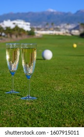 Two glasses with  bubbles white champagne or cava wine served on green golf club grass with mountains view during golf competition event or celebration in sunny day