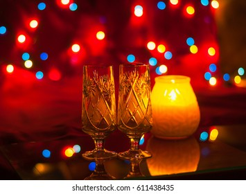 Two glasses by candlelight and a colorful bokeh on a red background