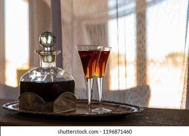 Two glasses an a carafe filled with red sherry in a room with a lot of sun, Namibia.