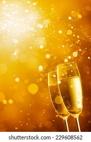 two glasses of champagne against gold bokeh background