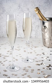 Two glasses of champagne with a champagne bottle in a bucket on grey background